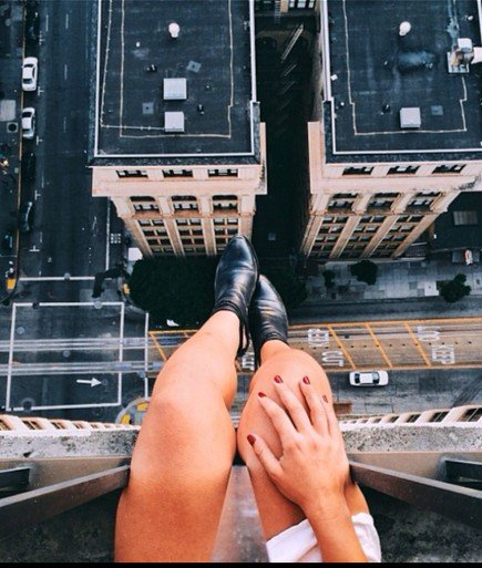 piernas de chica que está sentada en la azotea de un edificio