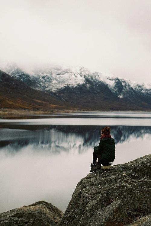 mujer sentada en unas rocas frente a una laguna