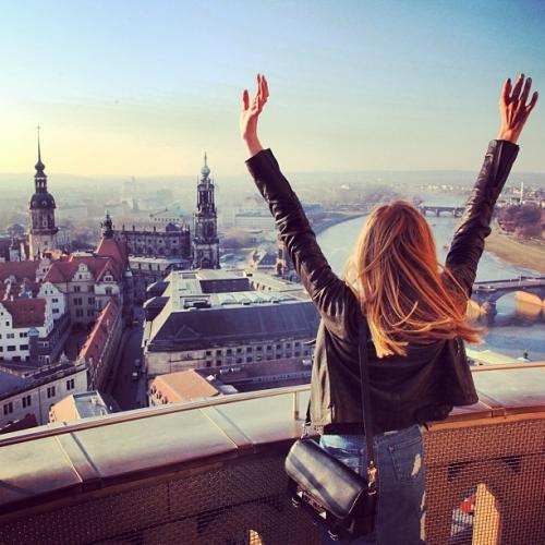 mujer viendo la ciudad y levantando los brazos