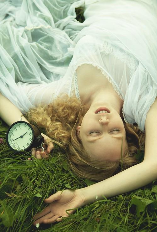mujer acostada sosteniendo un reloj