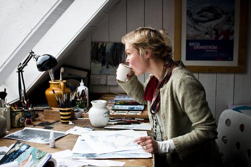 mujer sentada en un escritorio tomando café