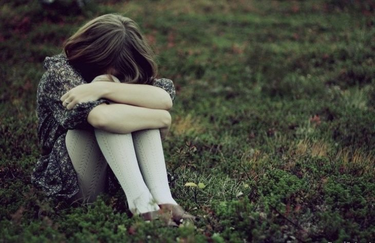 niña sentada en el pasto con las piernas cruzadas y llorando