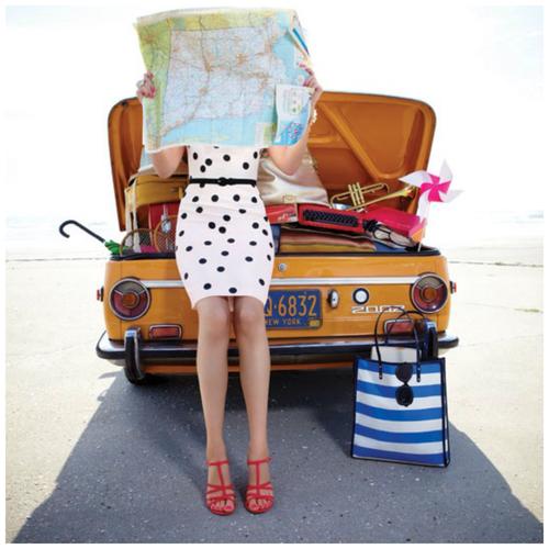 mujer sosteniendo un mapa en las manos sentada en un carro con maletas de viaje