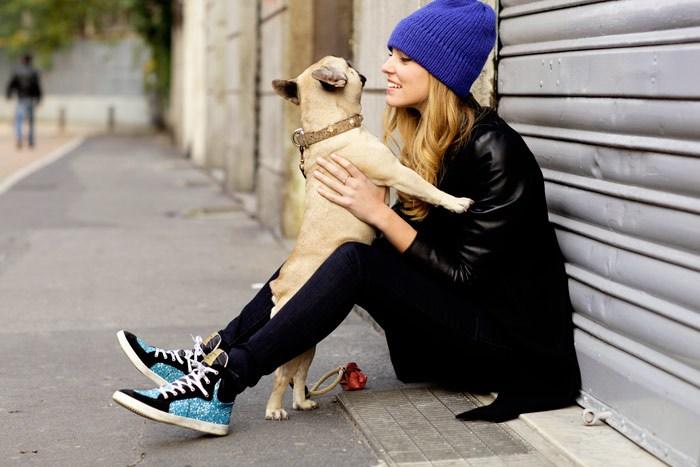 chica en la calle hablando con su perro