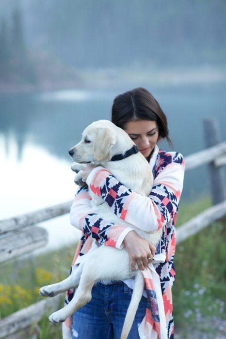 chica cargando a su perro a la orilla de un lago