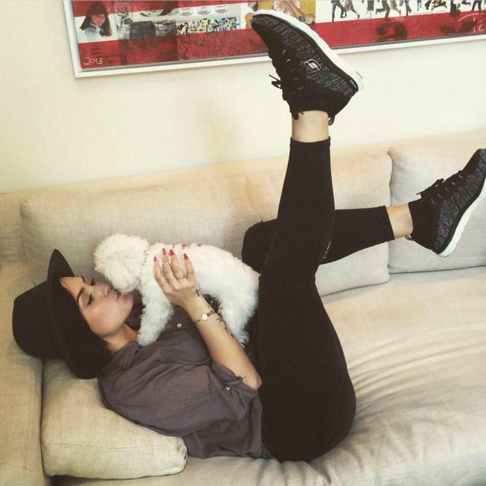 chica acostada en un sofá besando a su perro