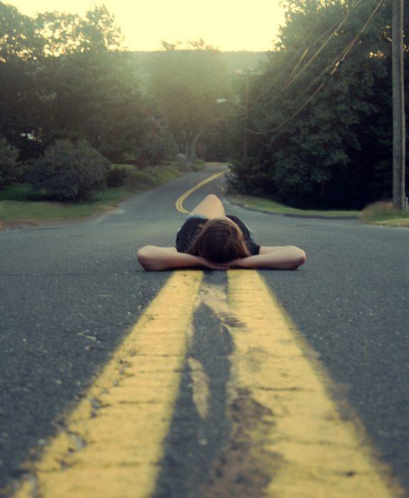 mujer recostada en medio de la carretera