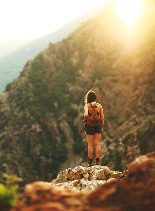 mujer parada sobre las montañas
