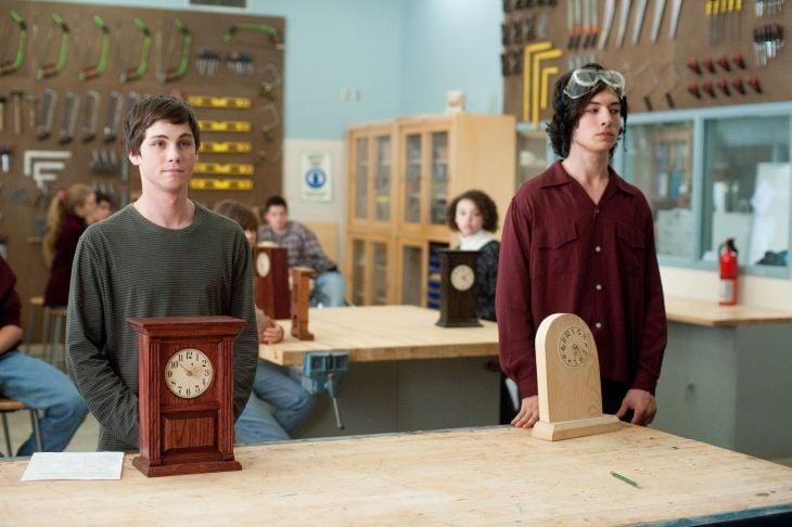 chicos parados frente a una mesa donde están dos reloj