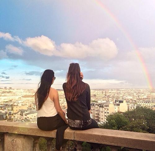 chicas sentadas viendo el arcoiris