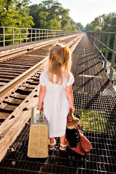 niña con una maleta en las manos caminando a un lado de las vías del tren