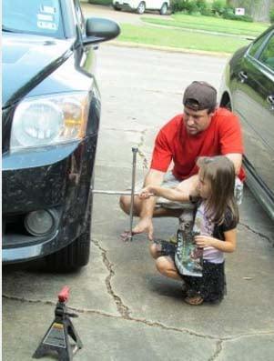padre enseñandole a su hija a cambiar una llanta