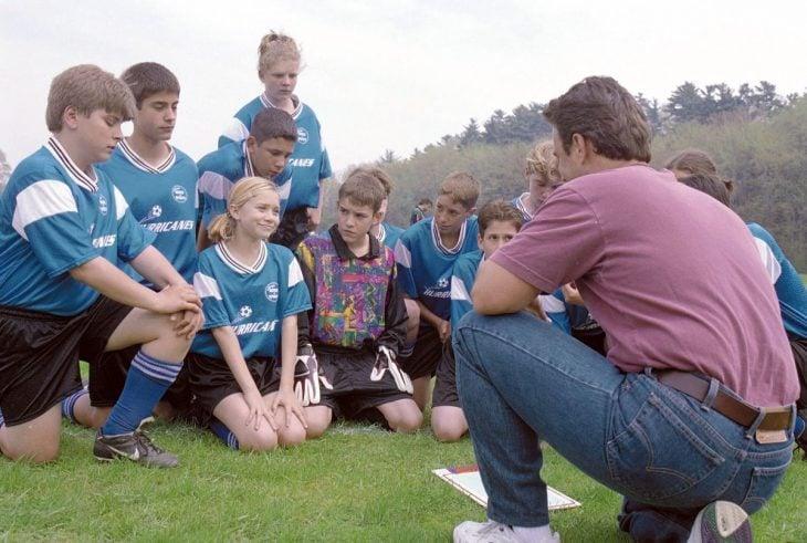 hombre reunido con un grupo de niños enseñándoles a jugar fútbol
