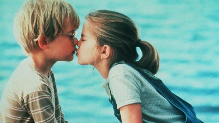 niños besandose frente al mar