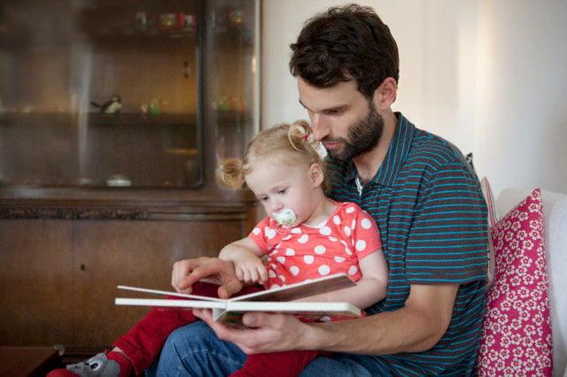 hombre leyéndole un cuento a su hija