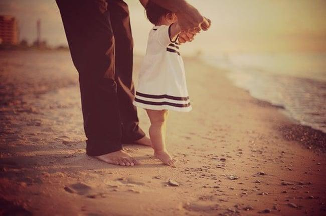 papa tomando de las manos a su hija mientras están en la playa