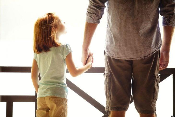 hombre tomando de la mano a su hija pequeña