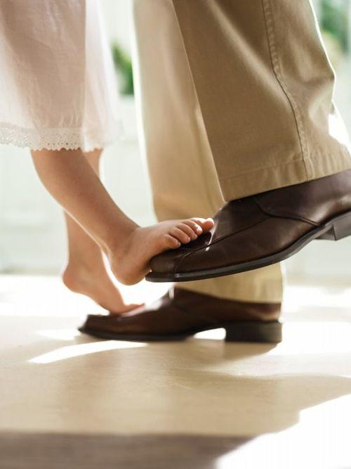 pies de una niña sobre los zapatos de un hombre