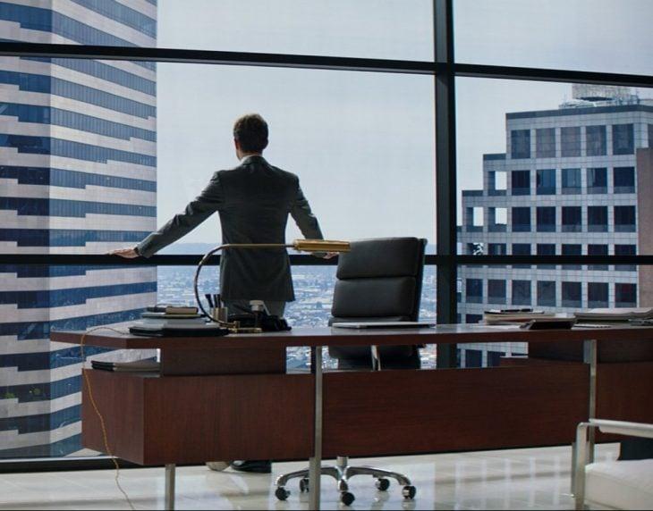 hombre recargado sobre un escritorio viendo la ventana