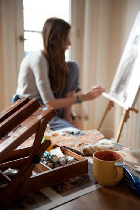 Chica en segundo plano pintando un cuadro