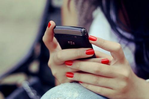 mujer sosteniendo un celular mientras escribe mensajes