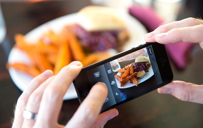 persona tomando una fotografía de su hamburguesa con el celular