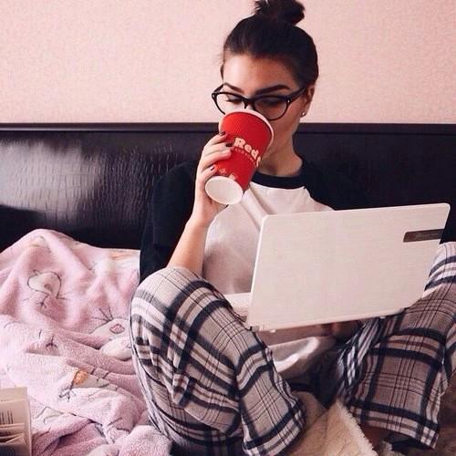 mujer sentada en la cama tomando café y revisando su computadora
