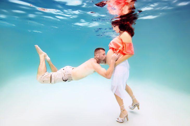 hombre besando el vientre de una mujer embarazada bajo el agua
