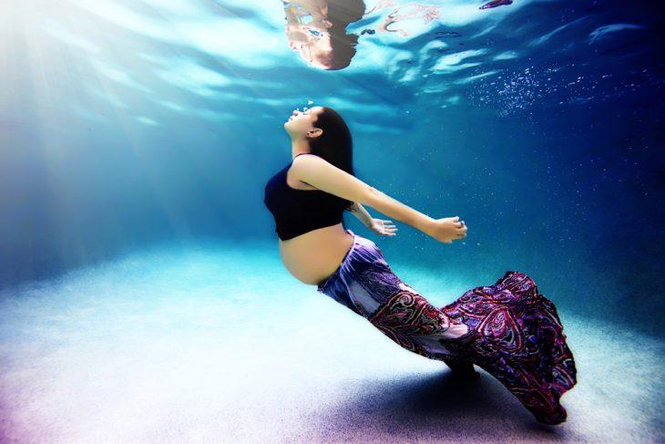 mujer con falda y top imitando la pose de una sirena embarazada bajo el agua