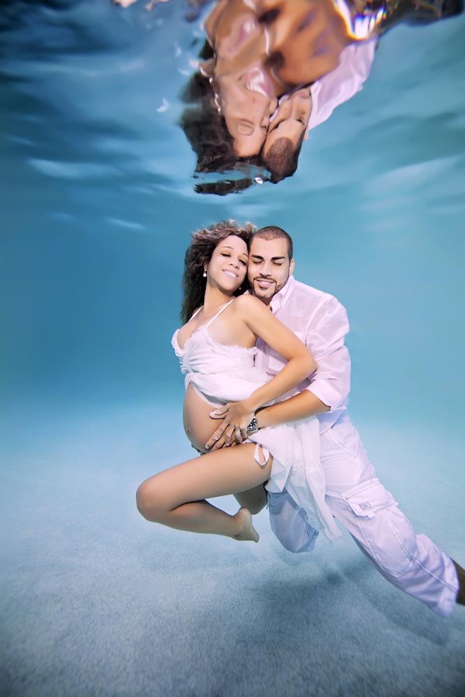 mujer embarazada siendo abrazada por su pareja bajo el agua
