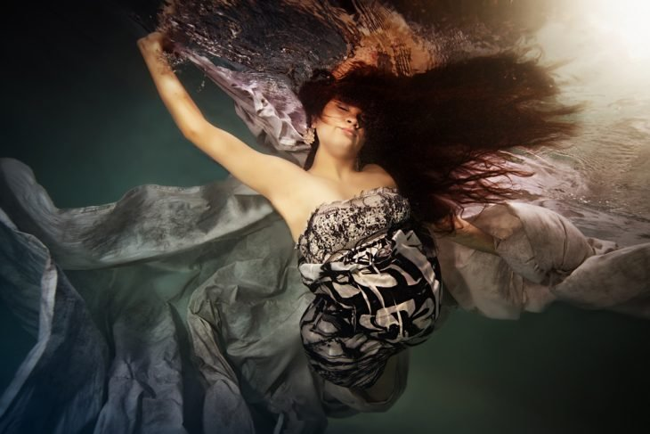 embarazada bajo el agua levantando los brazos