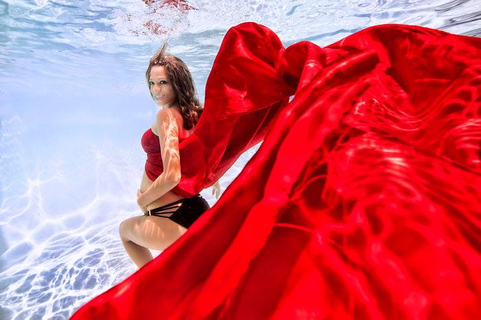 mujer embarazada tocándose el vientre vestida de rojo bajo el agua