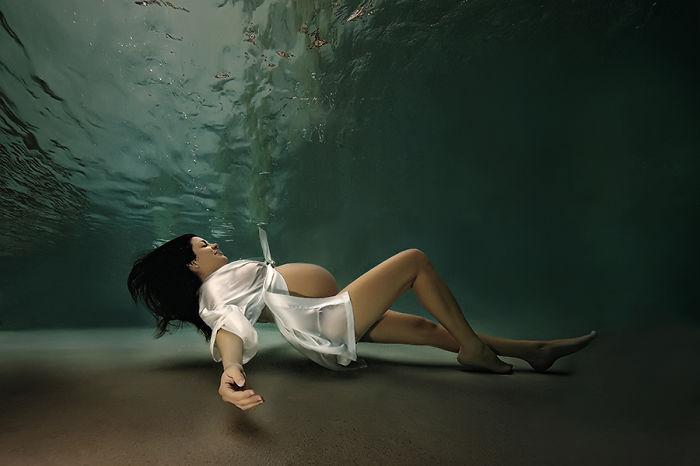 embarazada recostada bajo el agua usando un traje blanco