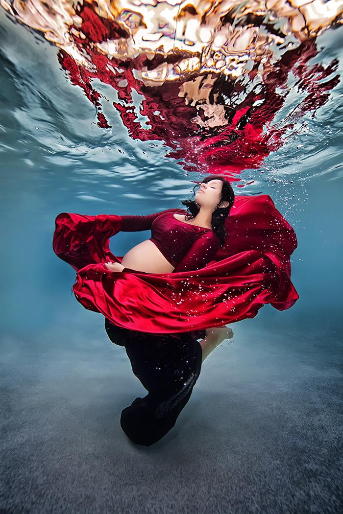 embarazada usando un vestido rojo bajo el agua