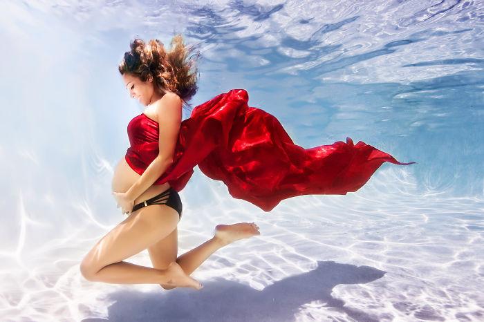 mujer embarazada vestida de rojo bajo el agua