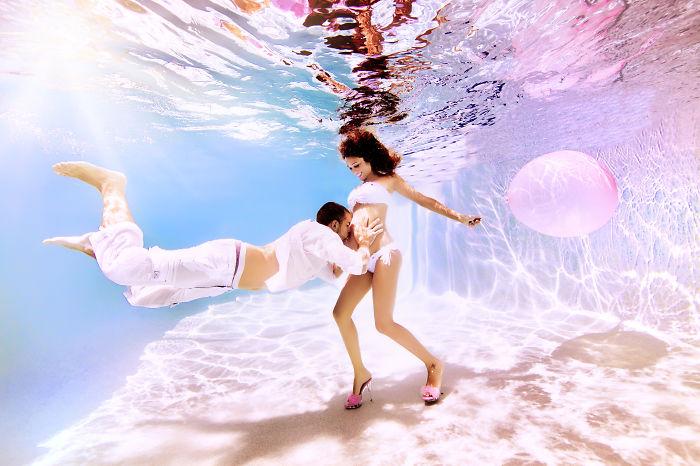 mujer embarazada parada bajo el agua mientras su pareja le besa el vientre