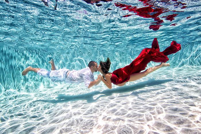 pareja de embarazados besandose bajo el agua