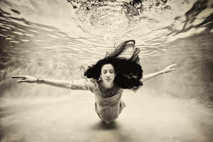 mujer embarazada bajo el agua con los brazos extendidos