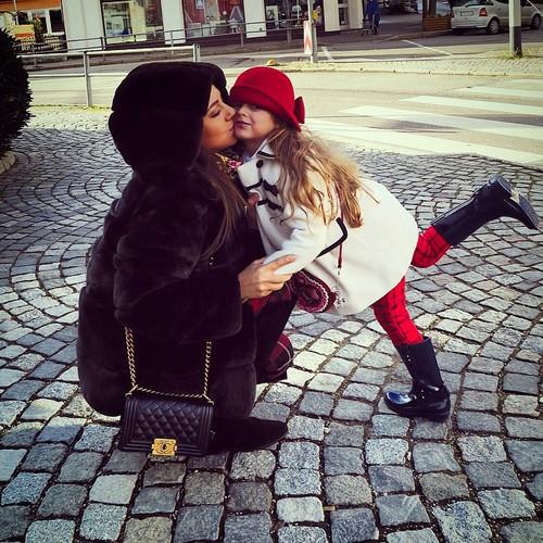 mamá besando a su hija en la mejilla