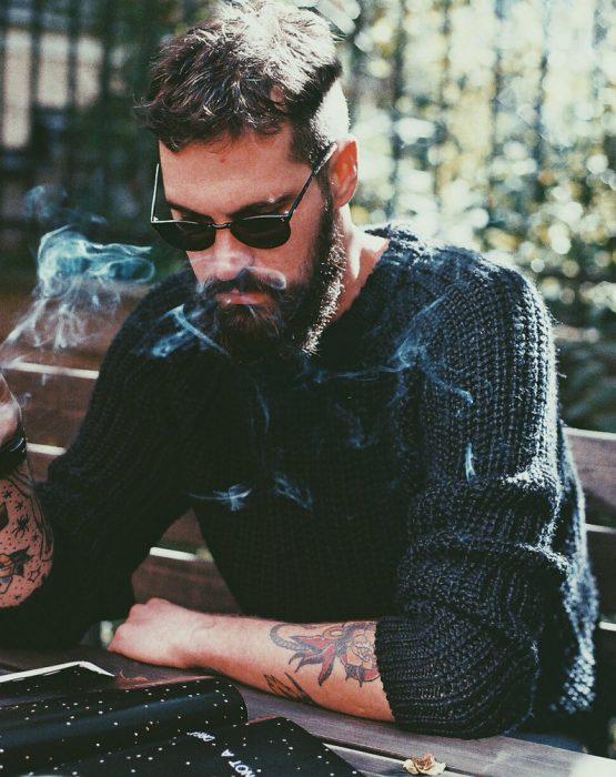 hombre sentado fumando mientras esta leyendo un libro