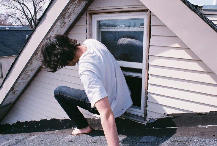 chico de playera blanca escapando por la ventana