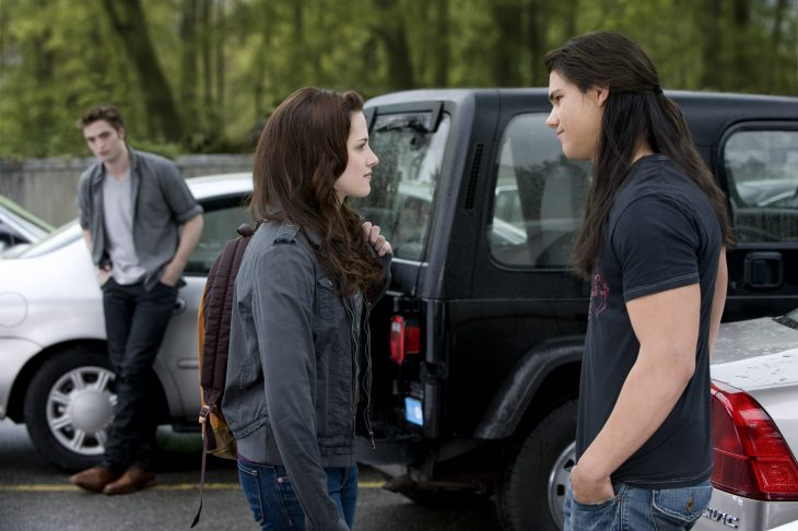 Una chica platicando con un chico en el estacionamiento mientras otro chico los observa de lejos