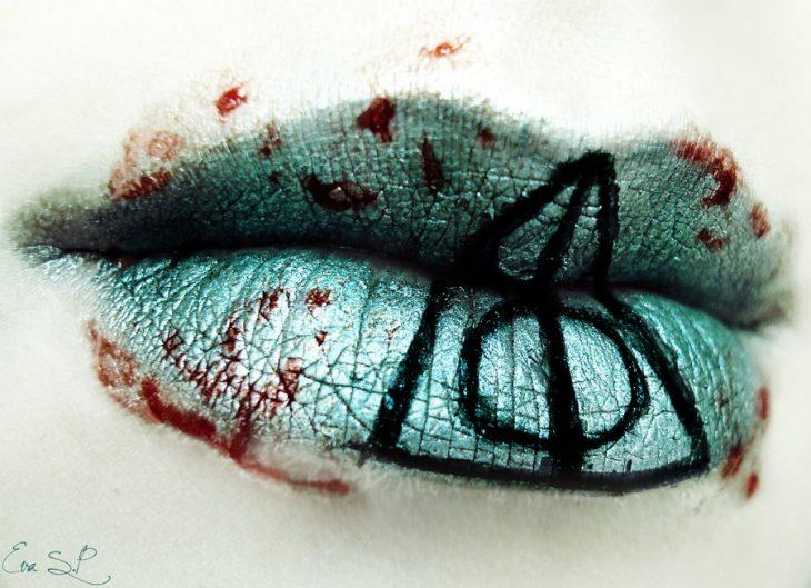 labios de color azul con sangre falsa al rededor con un símbolo en medio