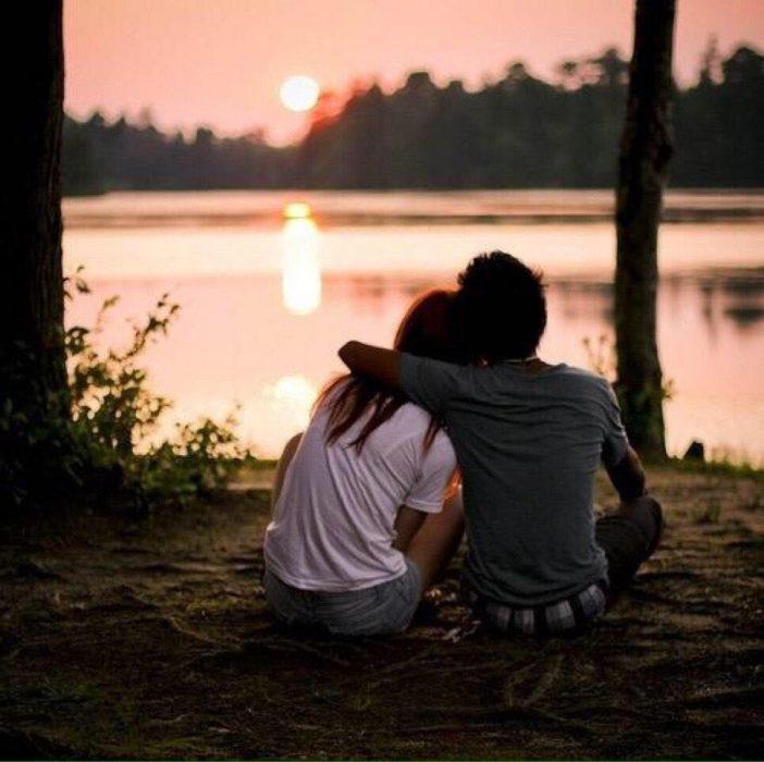 novios sentados en el bosque viendo el amanecer