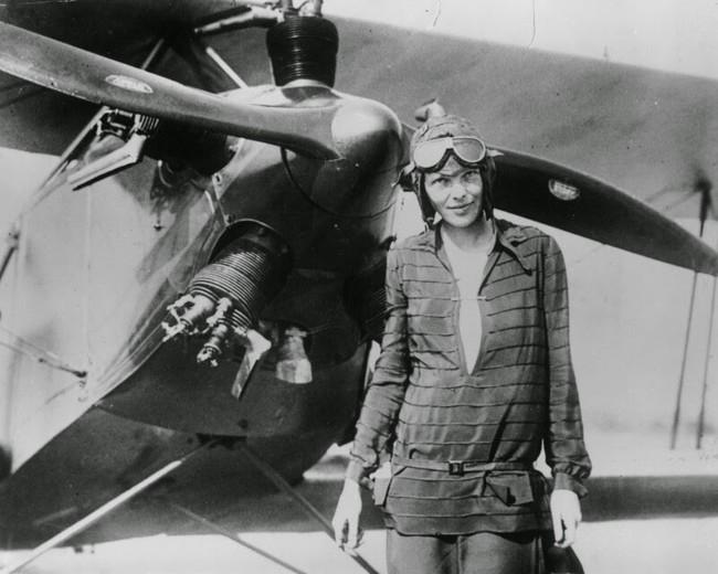 mujer posando a un lado de un avión