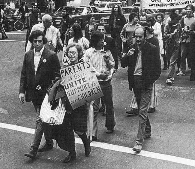 mujer marcando junto a un hombre sosteniendo carteles para expresarse