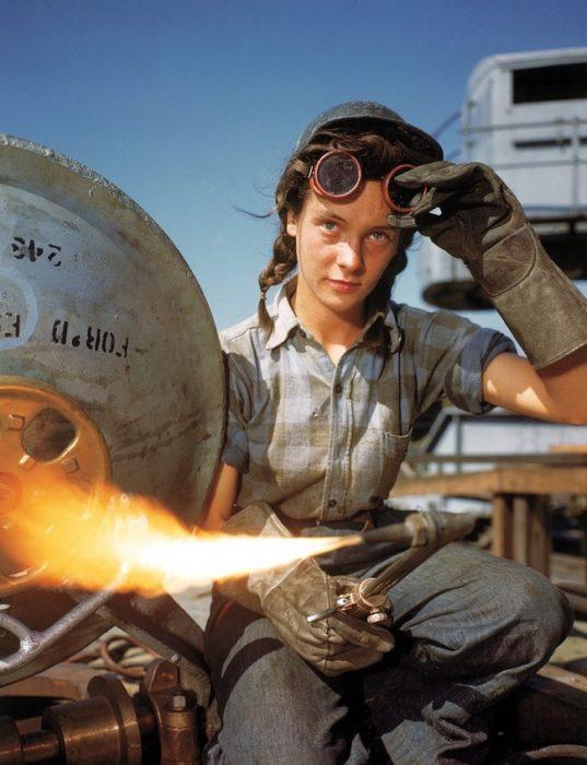 mujer sosteniendo un soldador para arreglar un avión en la segunda guerra mundial
