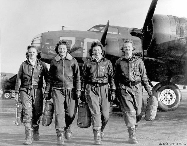 mujeres caminado junto a los aviones en la guerra