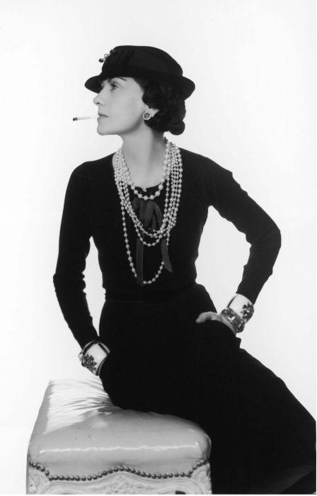 mujer sentada usando un vestido negro y perlas mientras fuma un cigarrillo