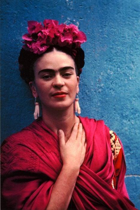 mujer con flores en la cabeza y reboso en el cuerpo tocándose el cuello recargada en una pared